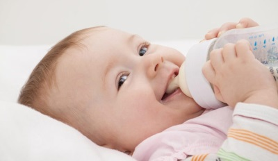 Ребенок ест смесь на основе козьего молока