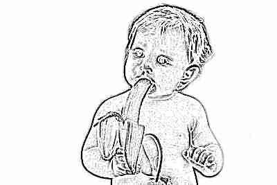 Ребенок ест банан с большим удовольствием