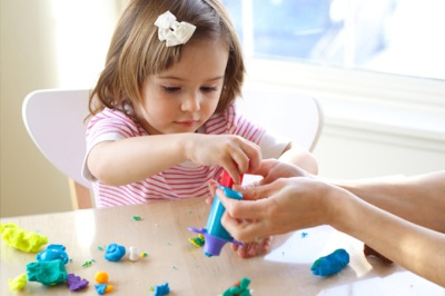 Девочка лепит из теста для лепки на кружке